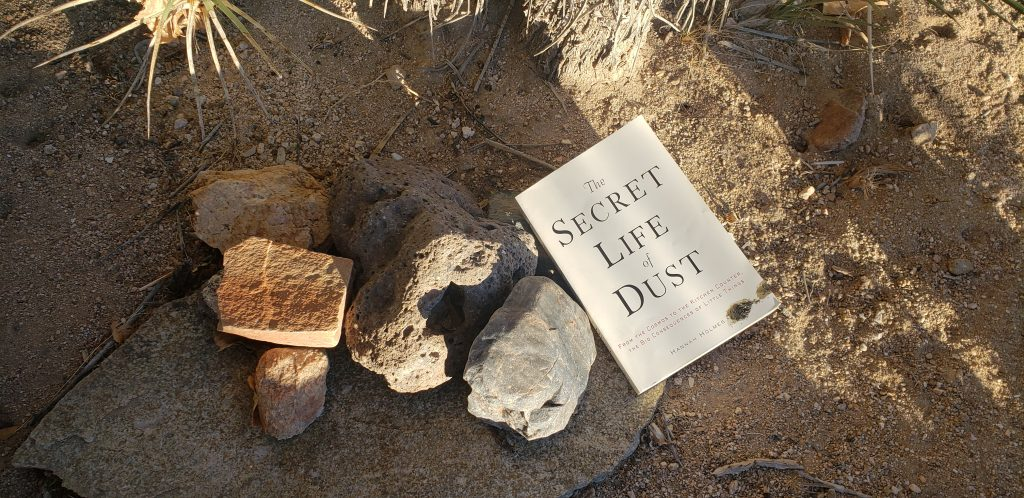 """The Secret Life of Dust"" book cover on the desert floor."